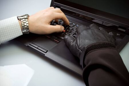 Security concept with businessman and hacker hands on laptop keyboard