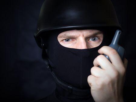 allegiance: Man in helmet and mask communicate by walkie talkie radio Stock Photo