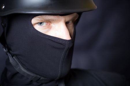 Man in helmet and mask staring at you over dark background photo