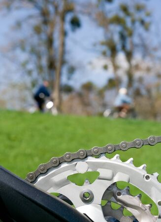 Chain and bicycle crankset over people riding bicycles photo