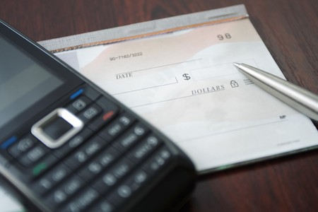 Blank check, pen and mobile phone on a table as a business concept photo