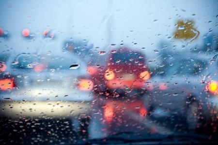 accidente transito: Parabrisas de coches con lluvia cae durante la tormenta y stoplights borrosas. Poco profunda de la profundidad de campo con enfoque en el centro del parabrisas con las luces rojas.