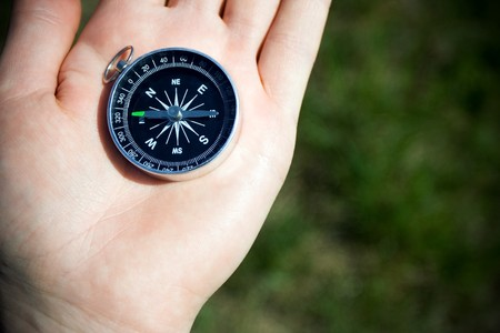 Classic compass on mans hand somewhere on trail during hiking. Green grass as a blurred background. photo
