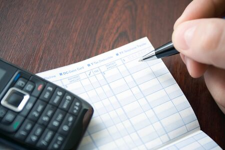 Man doing home finances on trasaction register notebook. Shallow depth of field with focus on pen. photo