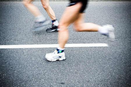 Man running in city marathon, blurred motion