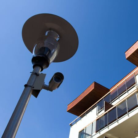 New apartments guarded by security camera over blue sky. photo