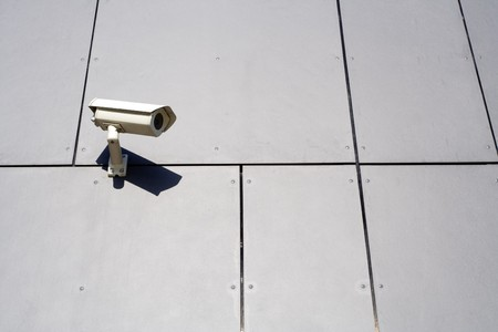 Security camera on gray abstract wall background photo