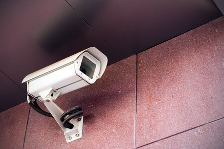 Office building with white security camera under a ceiling Фото со стока