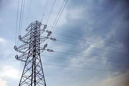 torres de alta tension: Silueta de la torre eléctrica y cielo tormentoso azul oscuro  Foto de archivo