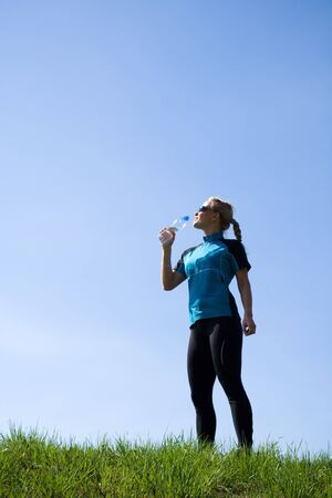 excercise: Woman taking a break and drinking water during running outdoors.