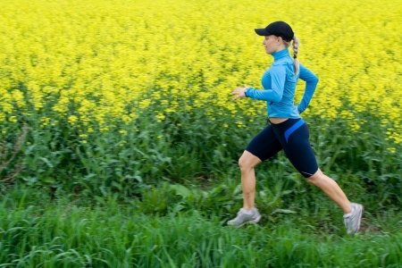 Athlete female runner training outdoors over yellow colza, motion blur.