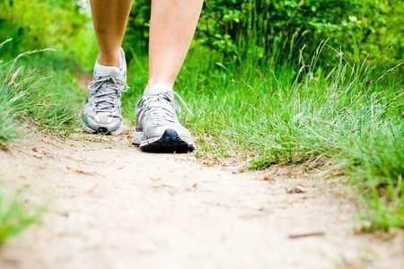 power walking: Woman walking on trail path in summer Stock Photo