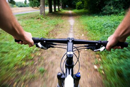 handlebar: Mountain bike rider riding real fast, motion blur Stock Photo