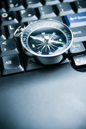 Computer keyboard and retro compass, business decision photo