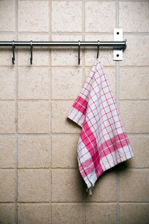 Kitchen utensils, cloth hanging alone on wall.
