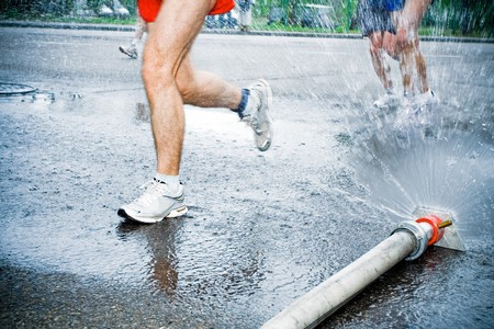 Marathon runners on wet city street under cold shower. Motion blur on running legs. Stock Photo - 7712476