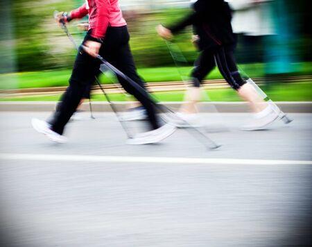 Mujer caminando sobre nórdico caminar raza en ciudad
