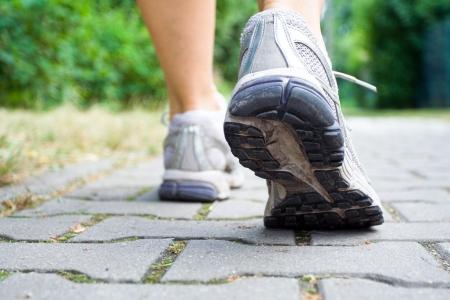 Mujer caminando sobre la acera, primeros planos de zapatos de deporte  Foto de archivo