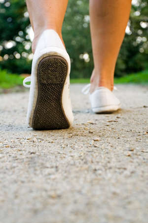 Woman exercise walking outdoors, shoes closeup photo