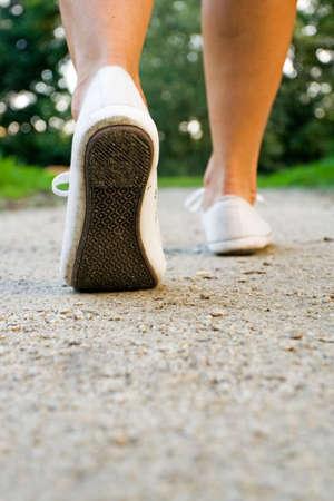 Woman exercise walking outdoors, shoes closeup photo