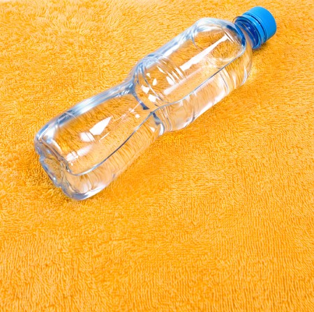 Water in bottle on orange background, fitness concept photo