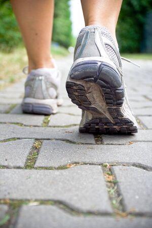Woman walking on sidewalk, sport shoe close-up photo