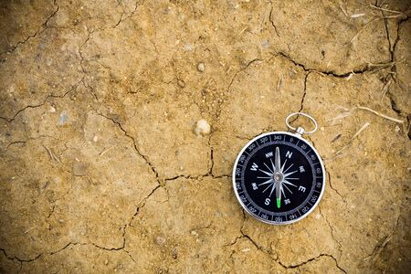 Compass and navigation background on dry sand photo