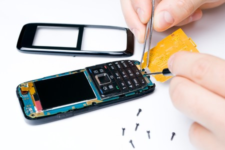 Mobile phone repair by electronic technician photo