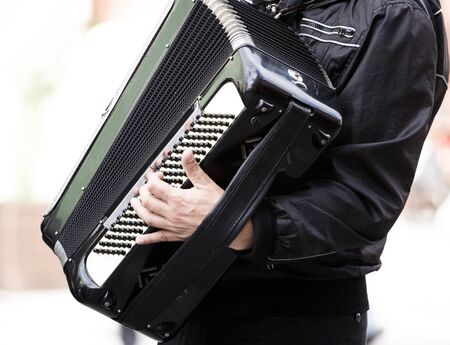 accord�on: Musician playing on accordion on city street