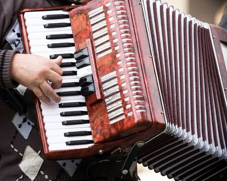 Musician playing on accordion on city street photo