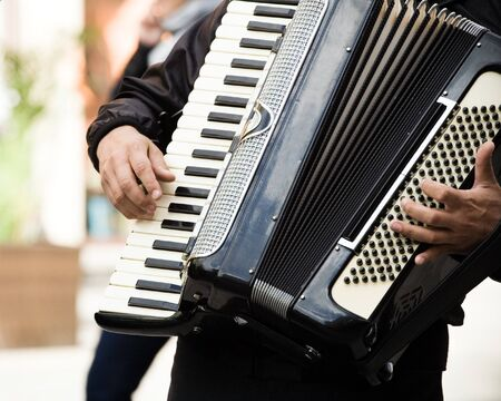Musician playing on accordion on city street