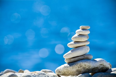 Close-up of white pebbles stack over blue sea