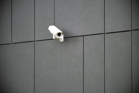 Security camera on dark modern building Фото со стока