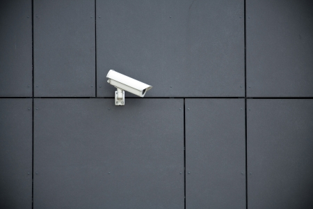 security monitoring: Security camera on dark modern building Stock Photo