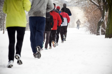 People running in park on snowy winter photo