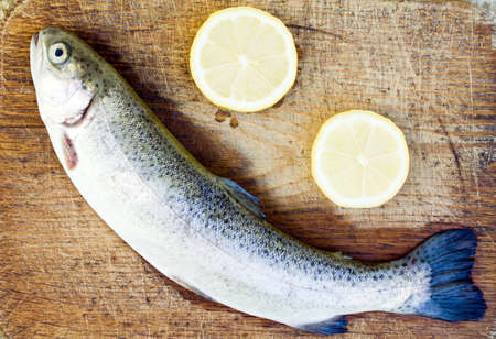 Prepering rainbow trout on wooden plate photo