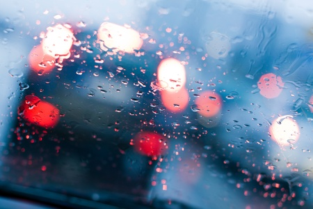 rain wet: Car windshield with rain drops during storm and blurred stoplights.Shallow depth of field with focus on center of the windshield with red lights.