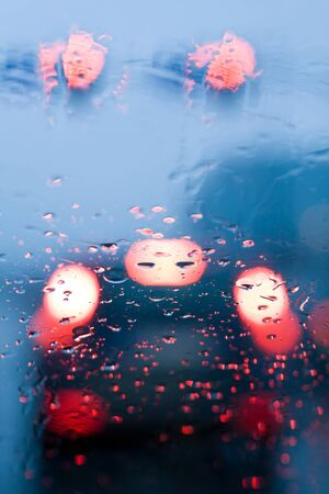 Traffic jam from inside a car during storm with rain drops on window. Shallow depth of field with focus on center of the windshield with red lights. photo