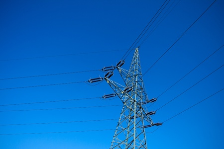 Electrical pylon silhouette and clear blue sky photo