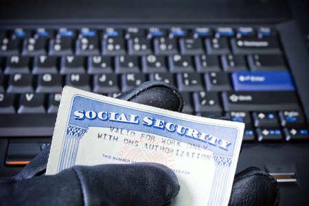 seguro social: Tarjeta de seguridad social en mano del hacker de equipo, robo de identidad Foto de archivo