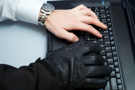 fraud: Hacker and businessman in one person working on a laptop computer Stock Photo