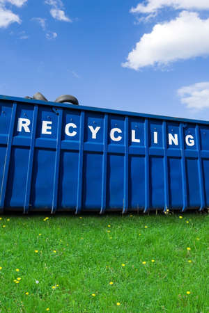 Recycling container with car tires on green fresh grass over blue sky Stock Photo - 9305966