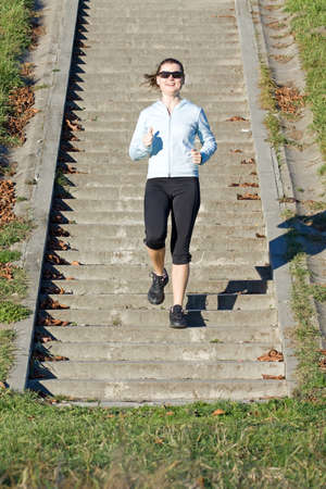 concrete stairs: Young woman running on stairs