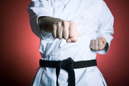 martial arts: Joven practicando karate sobre fondo rojo