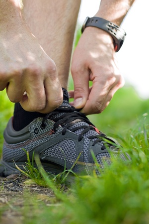 Tying sport shoe in green summer forest photo