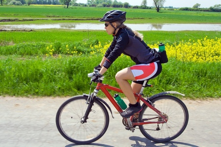 Young woman ride a mountain bike on summer day photo