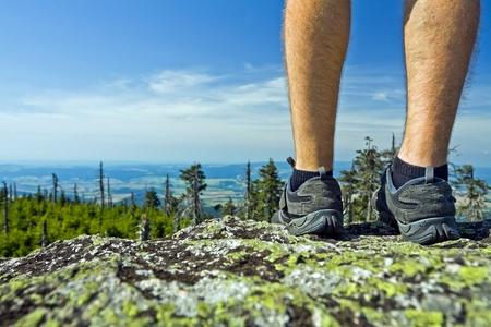 Legs of hiker on summit in mountains Stock Photo - 11017362
