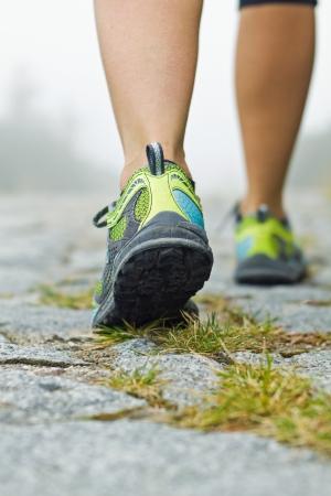 Mujer que camina en las montañas de zapatos deportivos Foto de archivo