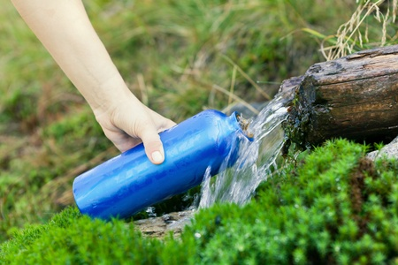 bottle with water: Woman filling water bottle from stream on hiking trip Stock Photo