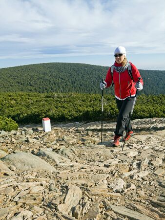 Woman on nordic walking trip in autumn mountains photo